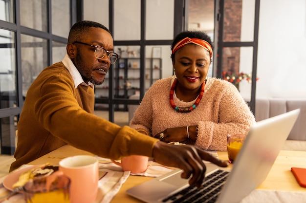 Appareil électronique. bel homme sérieux pointant sur l'écran de l'ordinateur portable tout en parlant à sa femme