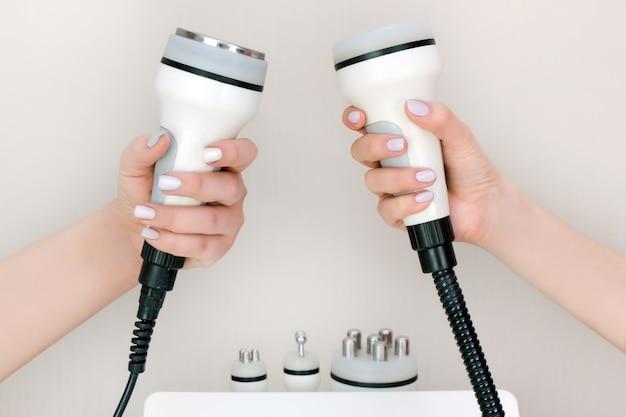 Appareil de massage dans la main d'une esthéticienne. levage rf, ultrasons, vide