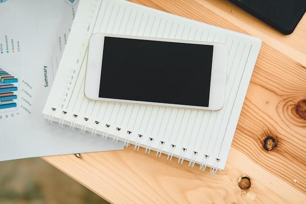 Appareil mobile à écran blanc en haut de la table avec rapport financier.