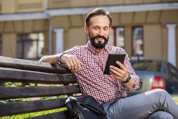 Appareil moderne. enthousiaste bel homme assis à l'extérieur en lisant un livre électronique