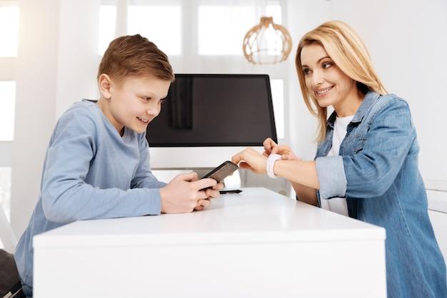 Appareil moderne. positive gai gentil garçon souriant et jouant sur son smartphone alors qu'il était assis en face de sa mère