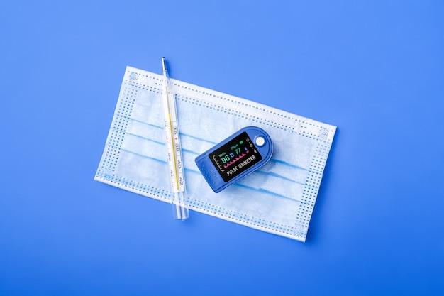 Appareil d'oxymètre de pouls près du thermomètre et du masque médical, concept de surveillance des soins de santé