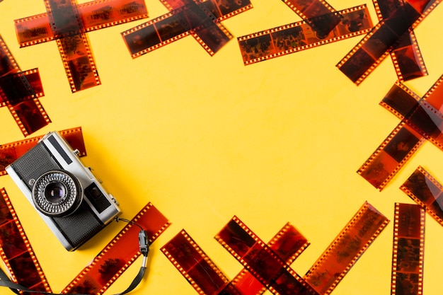 Un appareil photo à l'ancienne avec des négatifs sur fond jaune