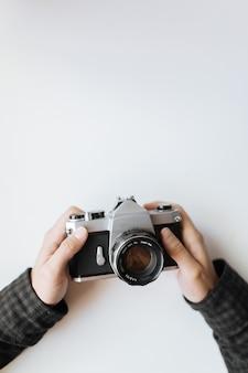 Appareil photo argentique vintage dans l'homme les mains sur un espace blanc