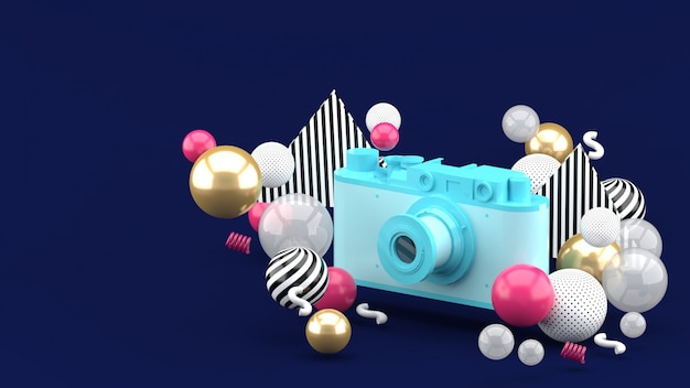 Appareil photo bleu entouré de boules colorées sur bleu. rendu 3d.