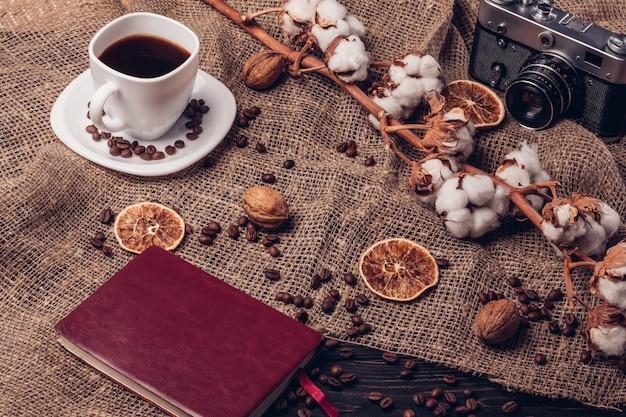 Appareil photo et bloc-notes de café noir chaud. nature morte