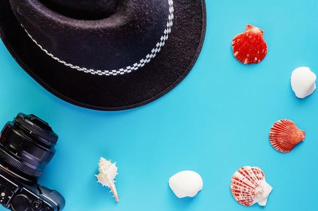 Appareil photo, chapeau noir et coquillages sur fond bleu pour les accessoires de voyage et la détente
