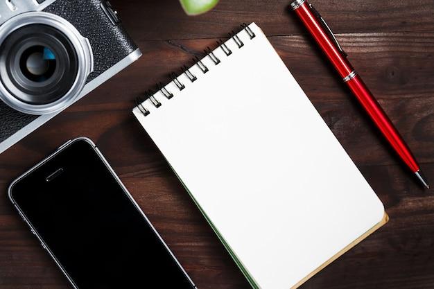 Appareil photo classique avec page vierge du bloc-notes et stylo rouge sur une table en bois marron foncé, table vintage avec téléphone et fleur verte