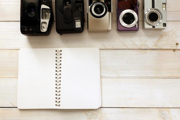 Appareil photo compact vintage avec une note vide sur le dessus en bois pour l'espace
