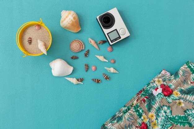 Appareil photo, coquillage, sable, pantalon de plage, fruit du dragon et smartphone sur bleu