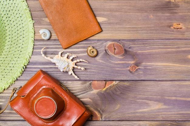 Appareil photo dans une étui, passeport, chapeau et coquillages sur un fond en bois