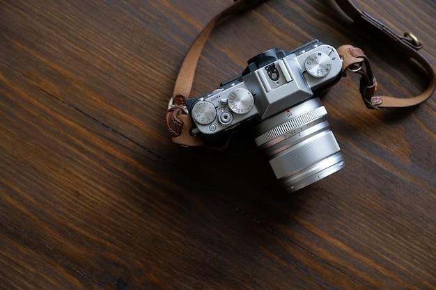 Appareil photo fujifilm vintage argent et noir avec bracelet en cuir marron sur une table en bois.