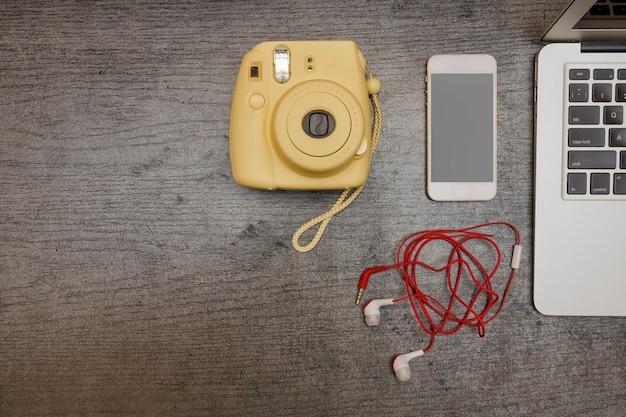 Appareil photo jaune, téléphone intelligent et casque. une partie de l'ordinateur portable. concept