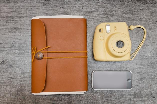 Appareil photo jaune, téléphone intelligent et ordinateur portable marron. concept