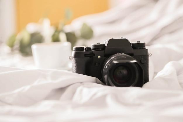 Appareil photo sur lit et tasse à café