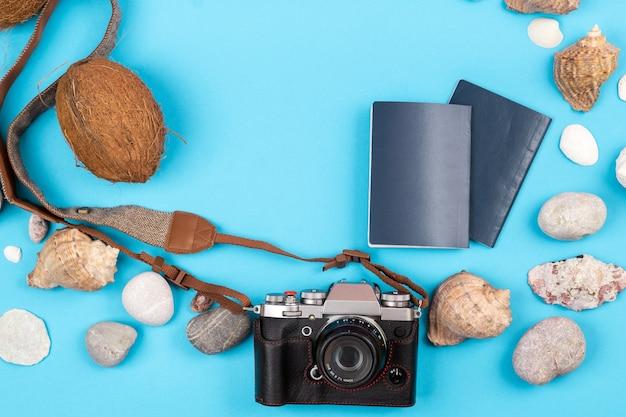 Appareil photo, noix de coco, coquillages et documents sur fond bleu. contexte pour le voyageur