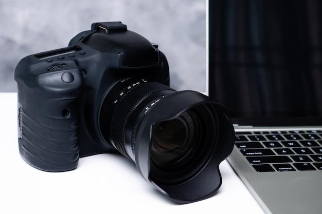 Un appareil photo numérique noir et un ordinateur portable sur une table.