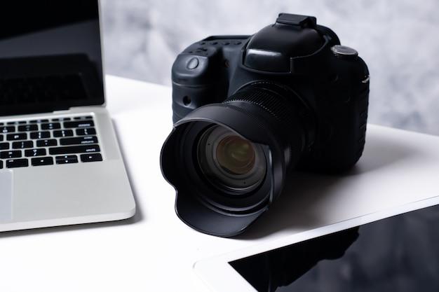 Un appareil photo numérique noir, une tablette et un ordinateur portable sur une table.