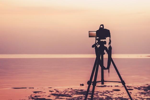 Appareil photo numérique professionnel reflex numérique sur trépied photographiant la mer, le ciel crépusculaire et le paysage nuageux. nature background.image, image à l'écran. appareil photo reflex numérique prise de vue paysage nature.appareil photo sur un trépied