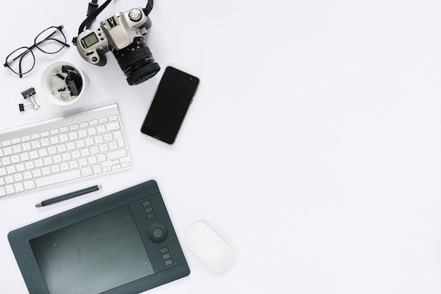 Appareil photo numérique; tablette numérique graphique; clavier; souris et téléphone portable sur fond blanc