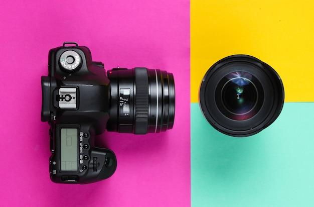 Appareil photo avec objectif sur une surface de couleur pastel.