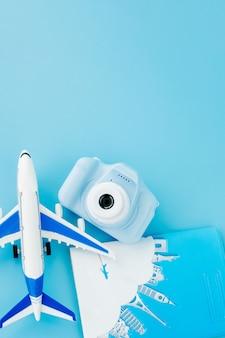 Appareil photo, passeport et avion sur mur bleu clair. concept d'été ou de vacances. espace de copie.