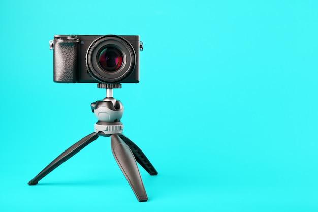 Appareil photo professionnel sur un trépied, sur fond bleu. enregistrez des vidéos et des photos pour votre blog ou votre rapport.