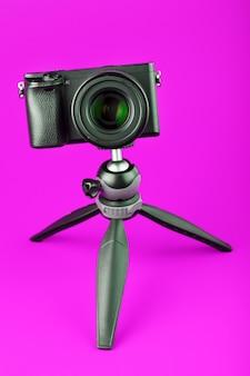 Appareil photo professionnel sur un trépied, sur fond rose. enregistrez des vidéos et des photos pour votre blog ou votre rapport.