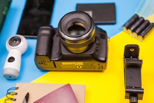Appareil photo reflex numérique sur fond bicolore à côté de différents accessoires