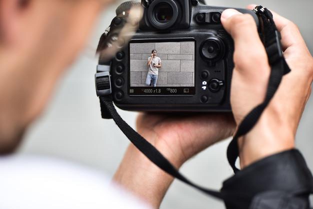 Appareil photo reflex numérique mono-objectif dans les mains. photographe tirant les mains en gros plan. un photographe homme fait des photos pour la photographie de stock. les mains masculines tiennent le gros plan de la caméra