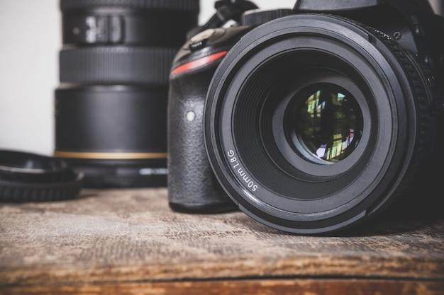 Appareil photo reflex numérique noir avec objectif principal de 50 mm 1,8 g sur une vieille surface de boîte vintage en bois brun