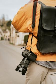 Appareil photo reflex numérique avec sangle accrochée à l'épaule du photographe