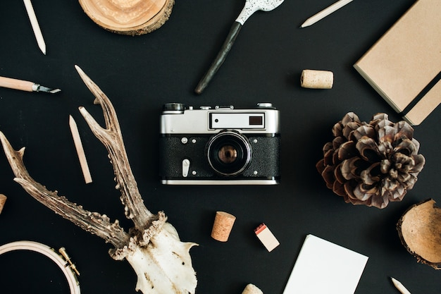 Appareil photo rétro, cornes de chèvre, cuillère à la main, journal d'artisanat, cône sur tableau noir.