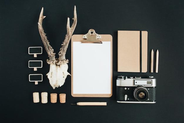 Appareil photo rétro, cornes de chèvre, presse-papiers, journal d'artisanat sur tableau noir.