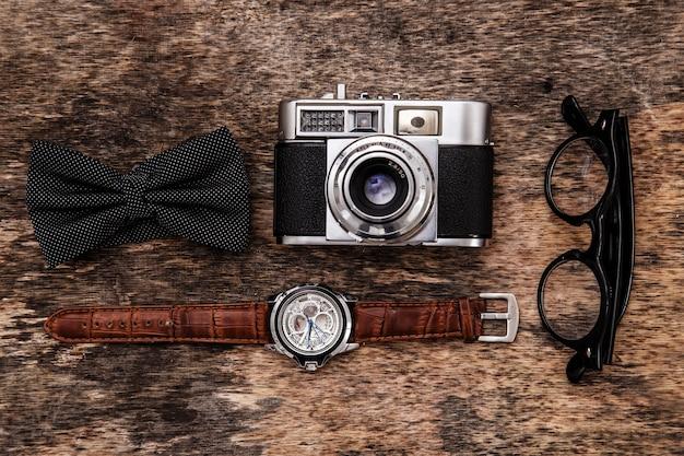 Appareil photo rétro, montre, noeud papillon et lunettes