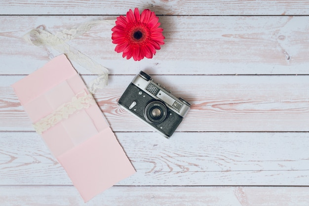 Appareil photo rétro près de papiers et de fleurs fraîches