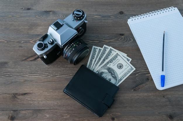 Appareil photo rétro, sac à main et bloc-notes avec un stylo sur une table en bois.