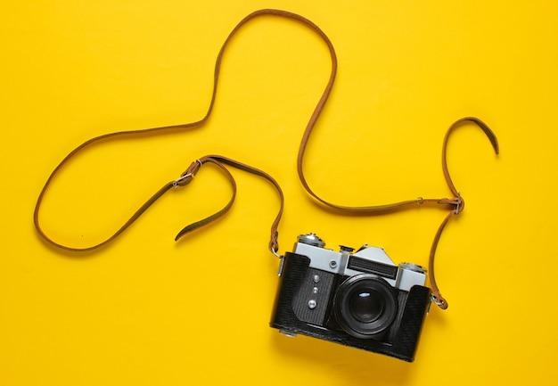 Appareil photo rétro vintage en cuir avec sangle sur jaune.