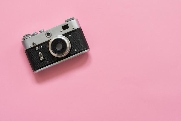 Appareil photo rétro vintage de plat poser sur fond rose. espace de copie, vue de dessus