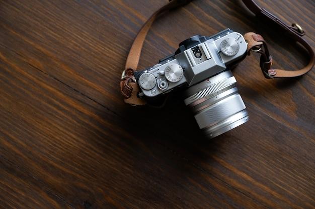 Appareil photo vintage argent et noir avec bracelet en cuir marron sur une table en bois.