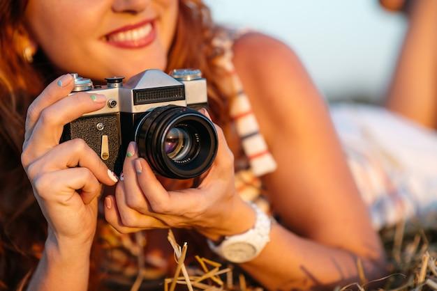 Appareil photo vintage entre les mains d'une belle jeune femme rousse, mise au point sélective, coucher de soleil