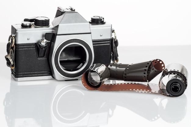 Appareil photo vintage avec un film 35mm sur blanc