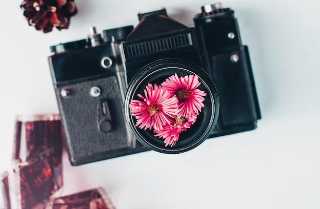 Appareil photo vintage, fleurs roses et film sur fond blanc