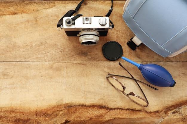 Appareil photo vintage sertie de sac et de verres sur planche de bois
