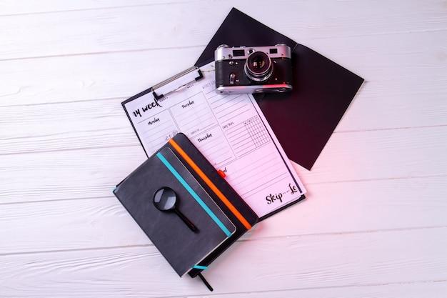 Appareil photo vintage vue de dessus avec presse-papiers et cahier. fond de bureau blanc.