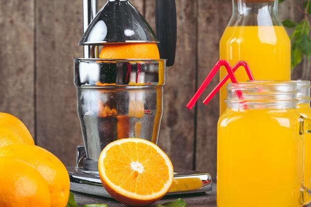 Appareil presse-agrumes orange sur la table de la cuisine se bouchent
