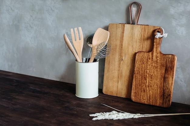 Appareils de cuisine.métal et bois. fourchette, cuillère et spatule sur un dessus de table en bois, contre un mur texturé gris.