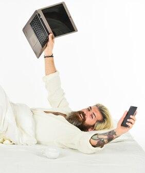 Les appareils électroniques émettent une lumière bleue artificielle qui peut supprimer la libération de mélatonine, une hormone induisant le sommeil. travail à domicile. ordinateur portable de travail hipster. travail à distance. achats en ligne. communication en ligne.