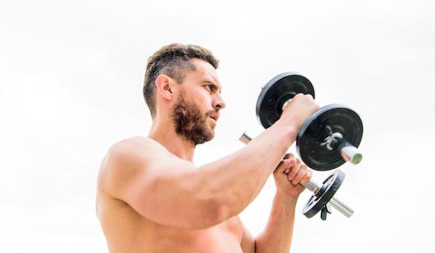 Appareils de fitness et de sport. corps athlétique. gymnase d'haltères. homme sportif avec des mains fortes. stéroïdes. homme musclé exerçant le matin avec haltères. succès. biceps parfaits. tout est possible.