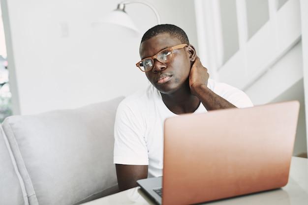 Apparence africaine d'homme à la maison devant le travail d'ordinateur portable